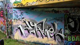 einGraffiti, verscknörkelter Schriftzug auf hellen Pastellfarben