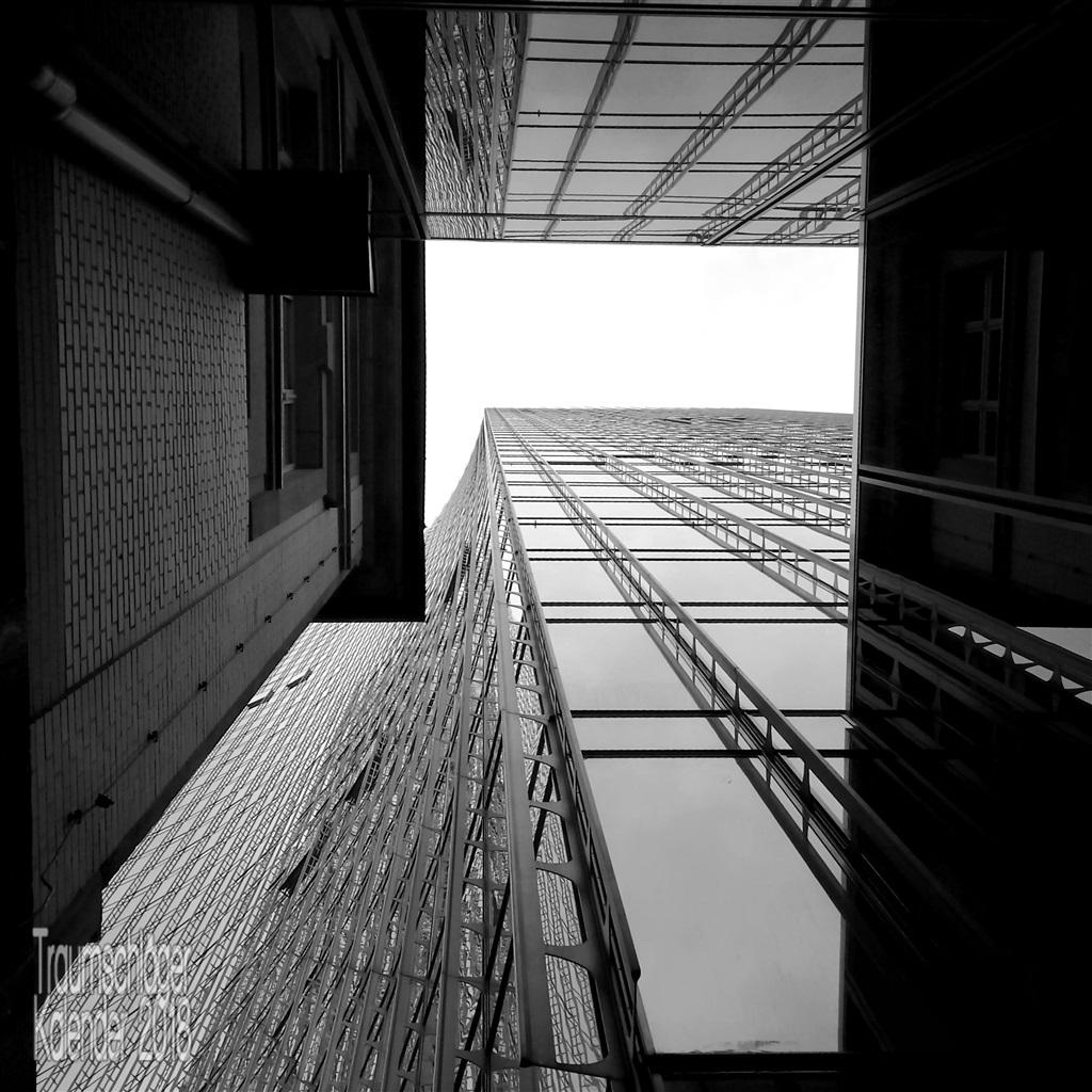 schwarzweiß-Aufnahme. ein altes 2-stöckiges Haus und daneben ein modernes Hochaus mit Glasfassade. Perspektive von unten senkrecht nach oben.