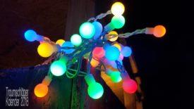 Detail-Foto: Im Dunkeln aufgenommenes Bild, in der schwachen Beleuchtung gerade noch zu erkennen eine Holzkonstruktion, daran befestigt das eigentliche Motiv des Bildes: Eine bunt beleuchtete Lichterkette. Die einzelnen Leuchten sind recht klein, wie kleine Knubbel, und leuchten in mehreren Farben gelb, orange, rot, blau und grün. An dieser Stelle befindet sich eine ganze Traube der Lichterkette auf einem Haufen, über 20 der Leucht-Knubbel.