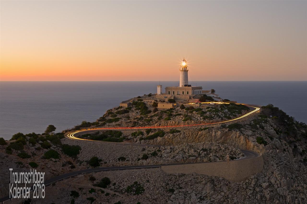 Landschaftsaufnahme: Ein Leuchtturm auf einem kargen, felsigen Hügel am Meer. vom Leuchtturm herunter windet sich in Serpentinen eine Straße, auf der die Lichter von Autos zu sehen sind, durch Langzeitbelichtung zu einem Lichtstreifen verwischt.
