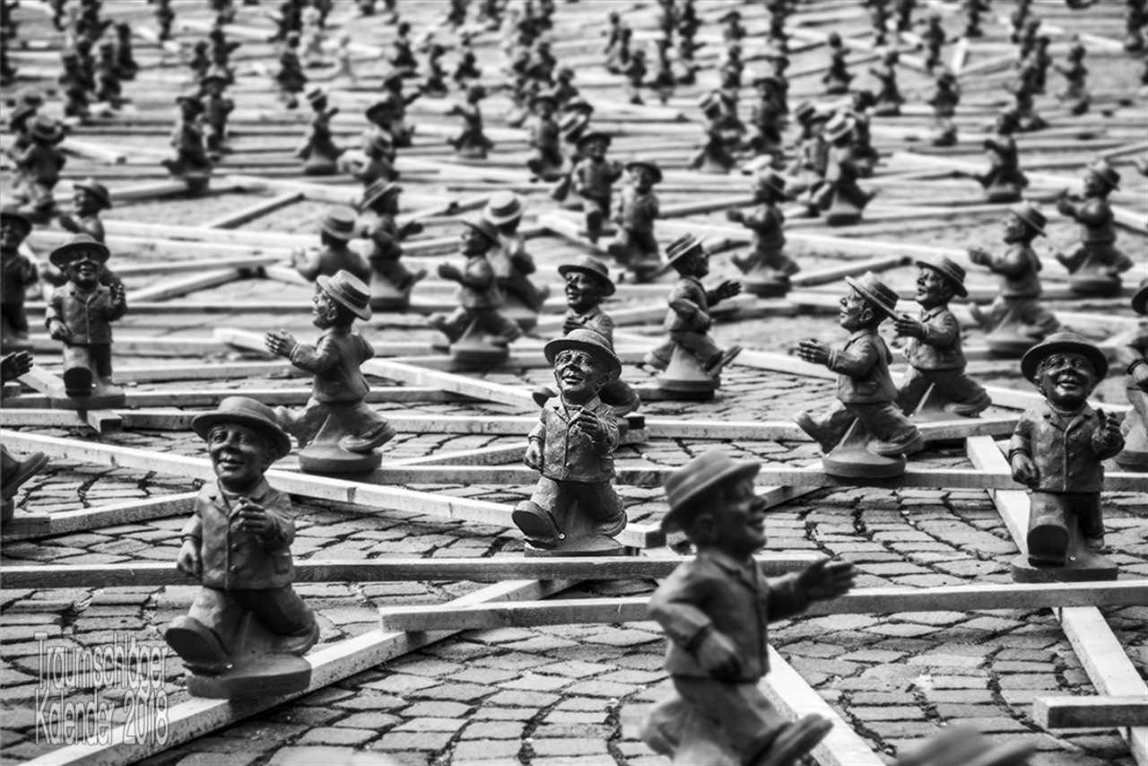 """Sschwarz-weiß-Foto einer Installation zum Tag der deutschen Einheit. auf Latten montiert sind viele (Hunderte?) etwa kniehohe Figuren des alten """"Ampelmännchens"""" der Fußgängerampeln der DDR. Die Männchen """"laufen"""" in lockerem Abstand in alle Richtungen durcheinander. Das Bild zeigt im Vordergrund ein paar der Männchen in Großaufnahme scharf, im Hintergrund erstreckt sich die Masse unschärfer werdend bis zum Horizont"""