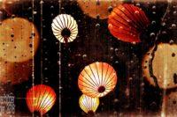 Bearbeitetes Foto: Papierlampions, beleuchtet und in der Luft schwebend. Das Foto ist versehen mit künstlicher Alterung, Fehlern und Flecken, und farblich im Sepiastil reduziert auf Töne von Orange und Gelb.