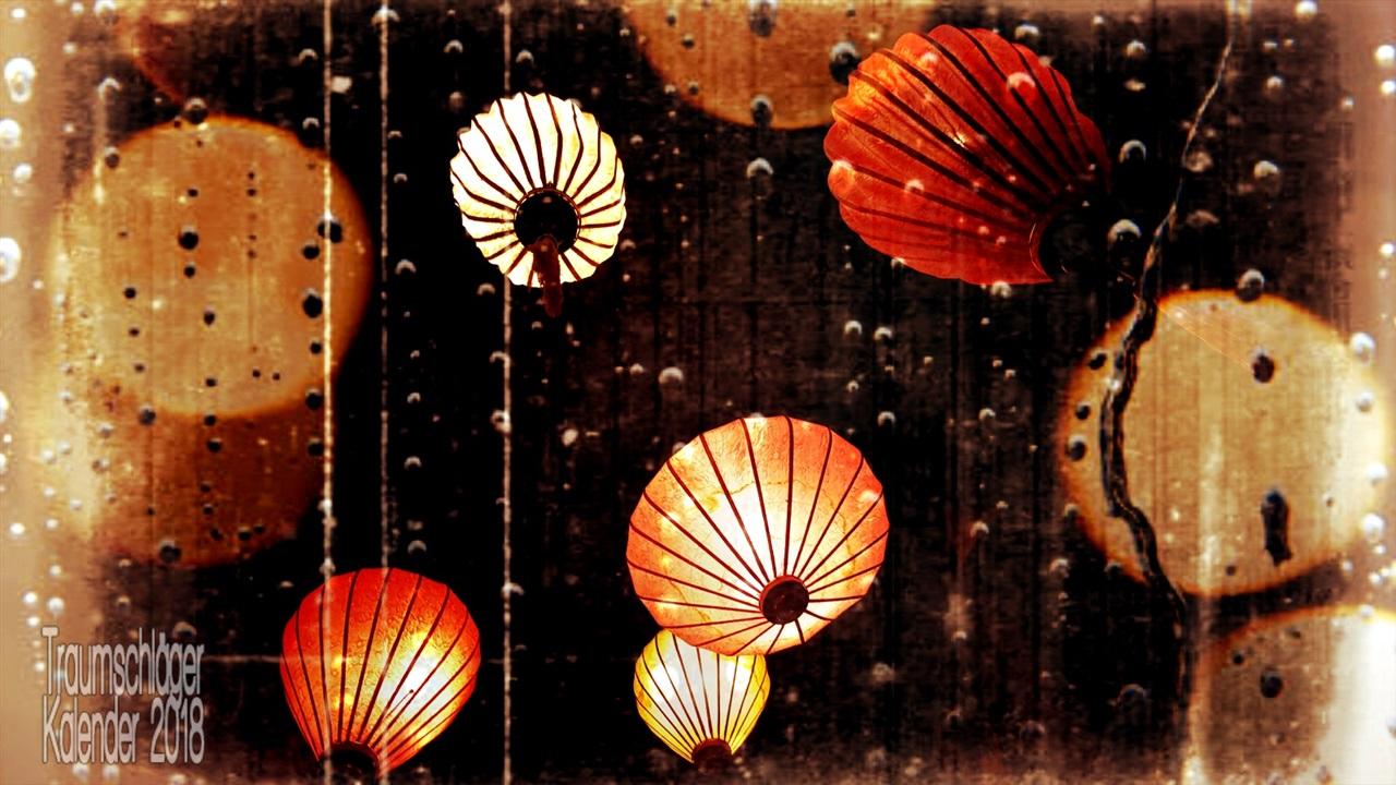 Papierlampions, beleuchtet, in der Luft schwebend. Foto bearbeitet, versehen mit Fehlern und Flecken, farblich reduziert auf Töne von Orange und Gelb