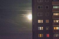 Mond mit zarten Wolken, davor ein Hochhaus mit ein paar dunklen und ein paar erleuchteten Fenstern