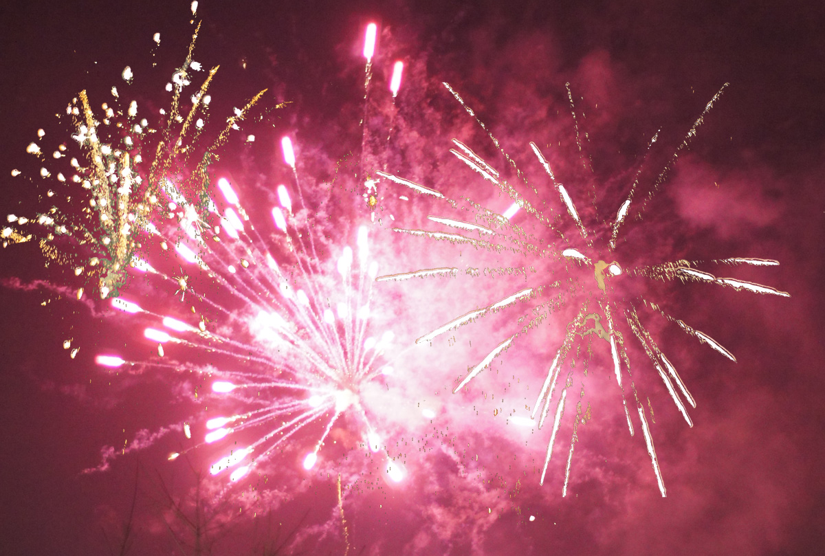 Feuerwerk: Große purpurrote Sternexplosion in der Mitte, links davon eine goldene nach oben gerichtete büschelförmige Fontäne, rechts davon goldgelbe Sternschnuppen
