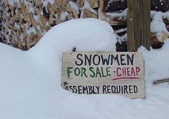 """Scherzbild: In einem großen Schneehaufen ein Schild """"Snowmen for sale - cheap (assembly required)"""""""