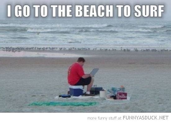 """Witzbild. Text oben """"I go to the beach to surf"""". Auf dem Foto selbst sitzt ein Mann am Strand. Auf einer Kühlbox, Strandutensilien um ihn ausgebreitet, und hat auf seinem Schoß ein Laptop und guckt konzentriert drauf."""
