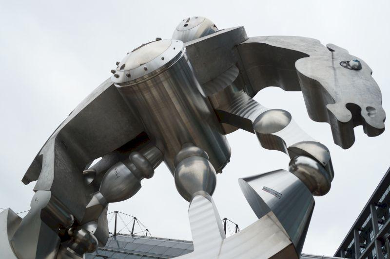Foto einer Plastik, die vorm Berliner Hauptbahnhof steht. ein stilisiertes Pferd aus Edelstahl, in einer runden Grundstruktur, die an einen Radreifen eines Zugs erinnert. Einzelne Glieder des Pferds sind verschieden gestaltet, aber alle sichtlich technisch bearbeitet.