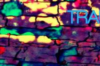 Bearbeitetes Foto: Ursprünglich Lichtflecken auf Straßenpflaster, überlagert mit blau, gelb, rot und einem Grundton von dunklem Violett. Am Rand der Effekt eines Filmnegativ-Streifens, der die Transportlöcher von Analogfilm nachempfindet.