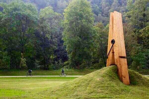 Übergroße hölzerne Wäscheklammer, die in einem Park ein Stück Wiese aufwirft und einklemmt. Möglicherweise eine Kunst-Skulptur