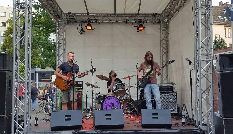 Hazard Dawn auf der Bühne bei ihrem Auftritt. Gitarrist, Schlagzeuger und Bassist
