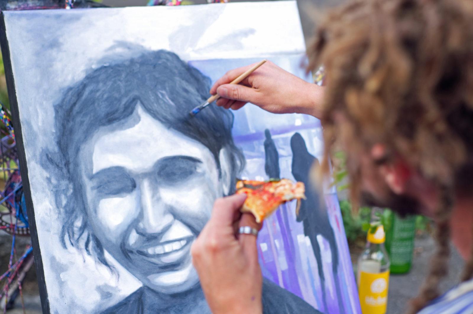 Zarathroxa schräg von hinten, hält in der einen Hand ein Stück Pizza, mit der anderen Hand malt er ein Bild, das er auf dem Straßenfest fertiggestellt hat.
