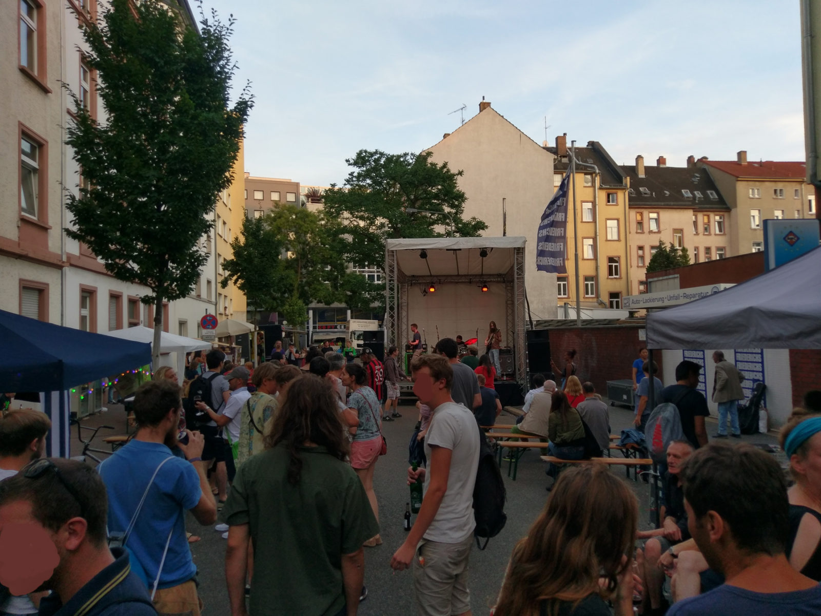 Totale über das Straßenfest. Im Vordergrund etliche Besucher von hinten, im Hintergrund vor den Besuchern die Bühne mit Hazard Dawn