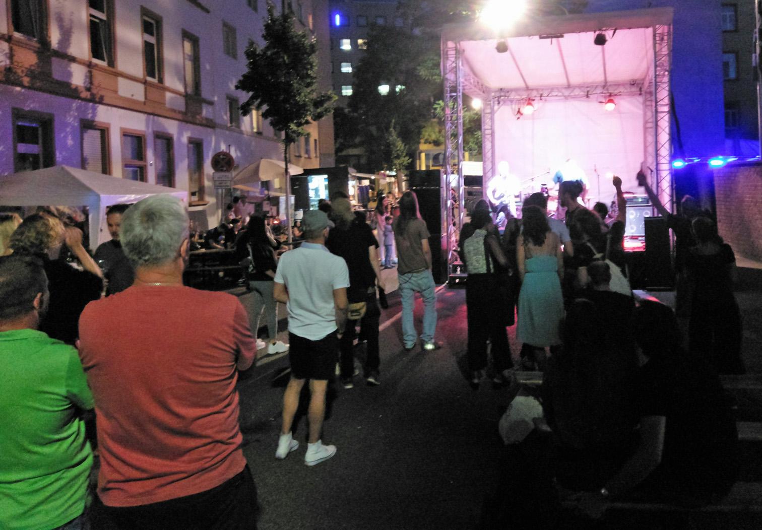 Bereich vor der hell erleuchteten Bühne in der Dämmerung. Auf der Bühne spielen Shadowpainter, vor der Bühne viele Besucher und tanzen und zuhören