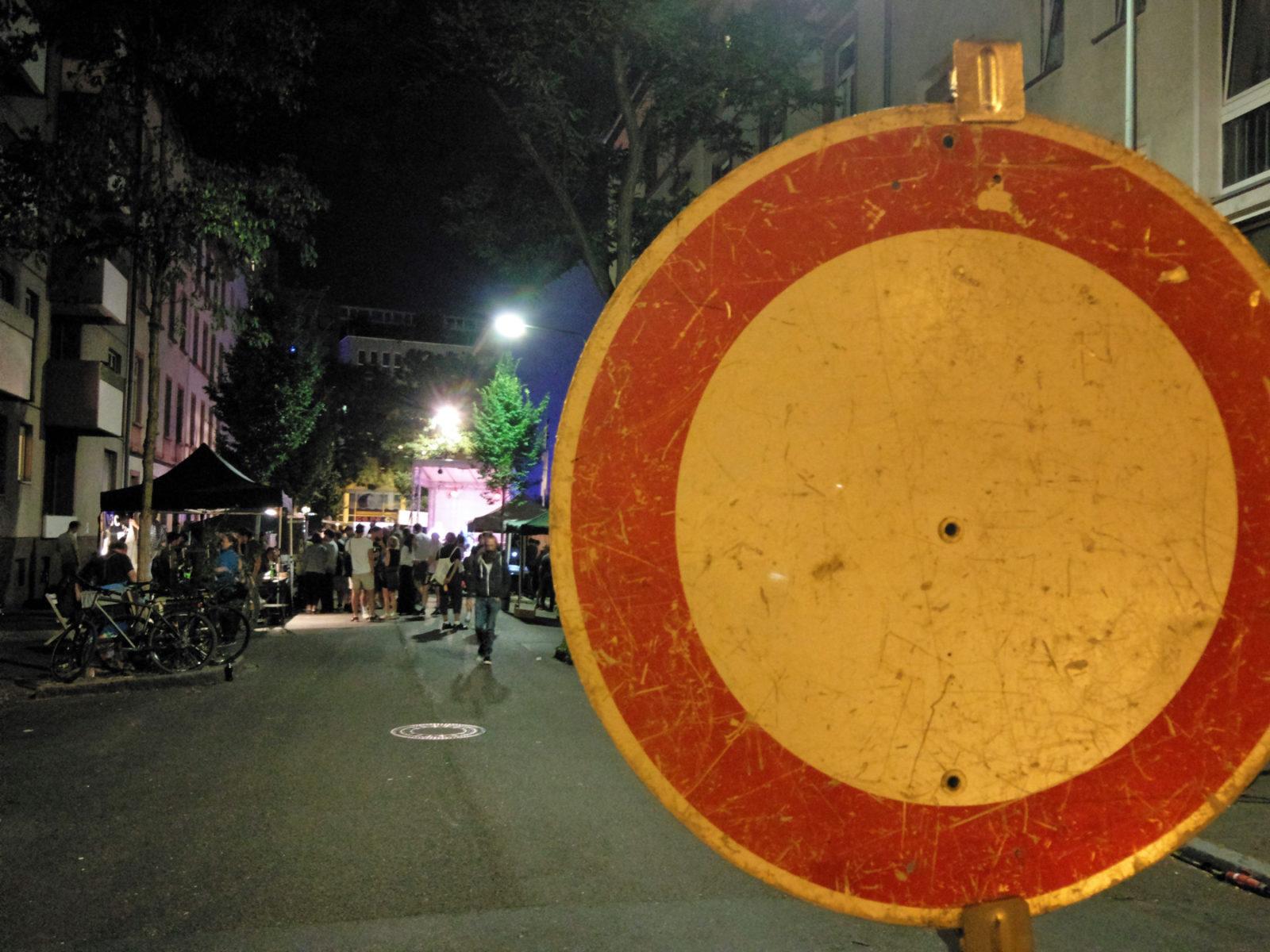 """im Vordergrund ein Verkehrsschild """"Verbot für alle Fahrzeuge"""", im Hintergrund das Straßenfest, mit Gruppen von Besuchern und der beleuchteten Bühne. Gedacht als Symbolik: """"Das war's, Schluss für heute"""""""