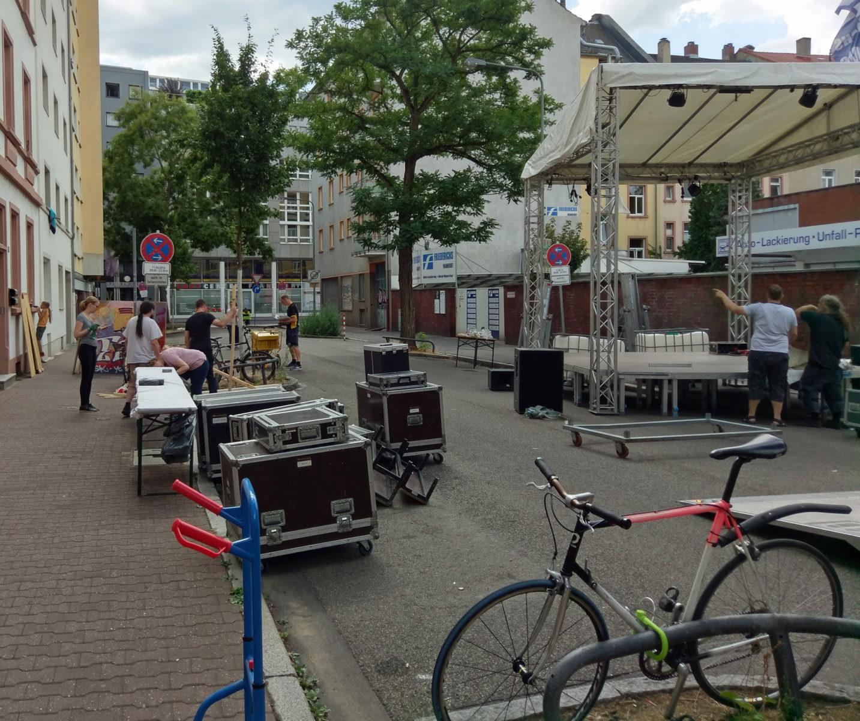 Aufbau des Straßenfests: Auf der Straße eine halbfertige Bühne, Verpackungskoffer von Bühnenequipment, Tische, eine Sackkarre und Gruppen von arbeitenden Leuten
