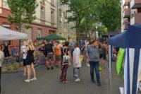 Totale über die Straße, am Rand Schirme und Pavillons der Stände, in der Mitte Besucher, das Fest ist gut gefüllt