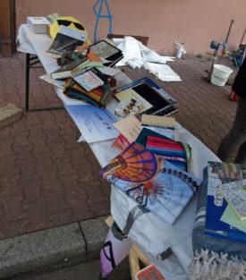Die Tombola-Preise des Traumschläger Kollektivs. Fotos auf Leinwand und gerahmt,Taschen, Bücher, Zeichenutensilien usw. in mehreren Stapeln aufgebaut und präsentiert