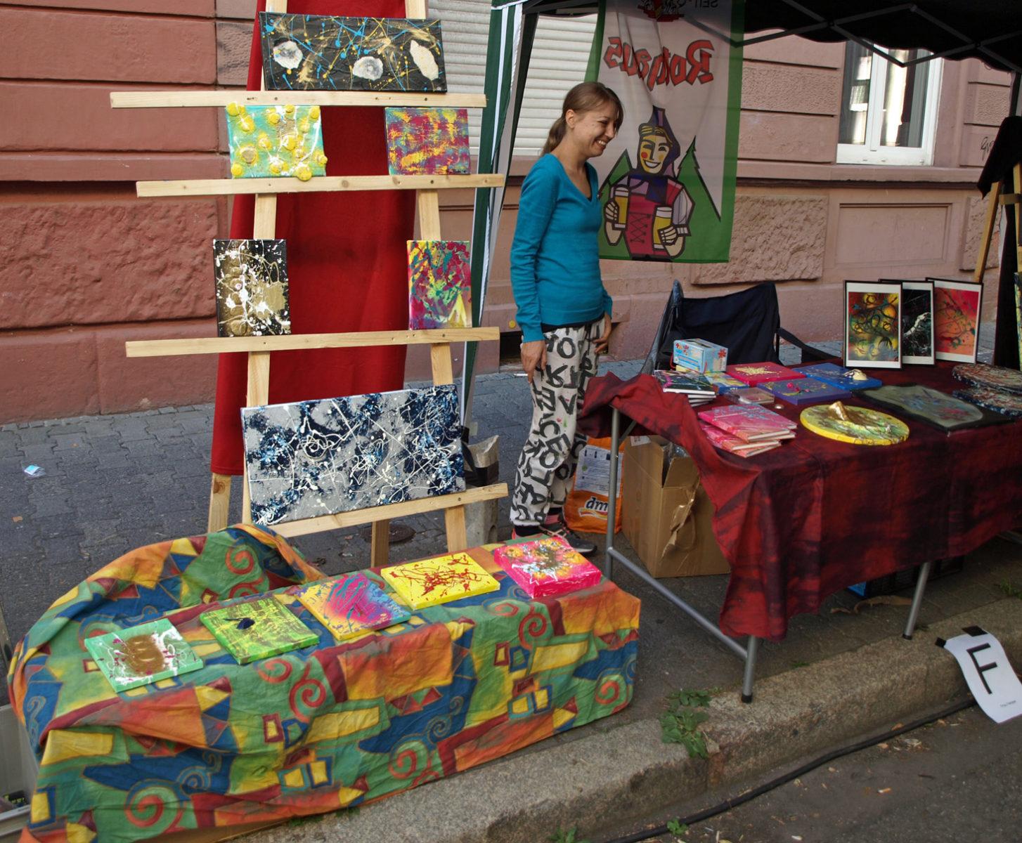 Frau Fenster an ihrem Präsentationsstand. Tisch und Ständer mit Bildern und gestalteten Gegenständen im Design von Frau Fenster mit abstrakten, farbenfrohen Mustern