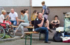 Zwischen anderen Besuchern sitzt Joachim Durang auf einer Bank und beobachtet vor seinem Auftritt das Fest