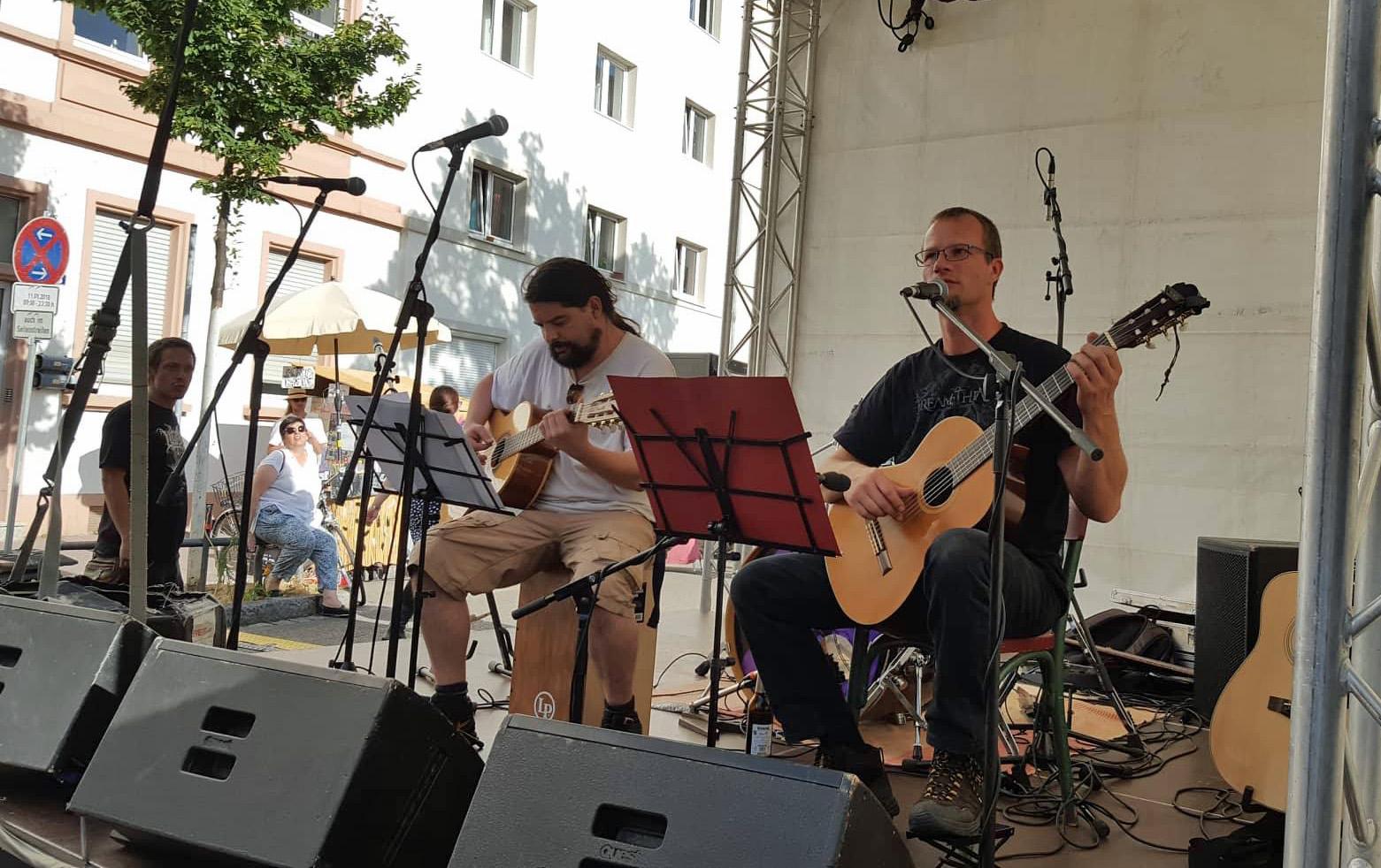 Speerträge und Royce auf der Bühne, von schräg seitwärts. Beide spielen Gitarre, Speerträger singt, neben der Bühne interessierte Zuhörer