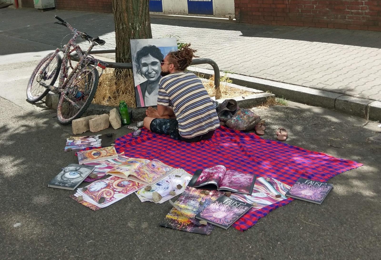 Zarathroxa sitzt unter einem Baum auf einer bunten Decke. Um sich herum liegen Werke und Bücher von ihm, vor ihm ein Bild, an dem er malt.