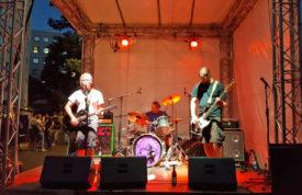 Shadowpainter aus Gießen bei ihrem Auftritt. Gitarrist, Schlagzeuger, Bassist. Im Hintergrund Gruppen von Besuchern
