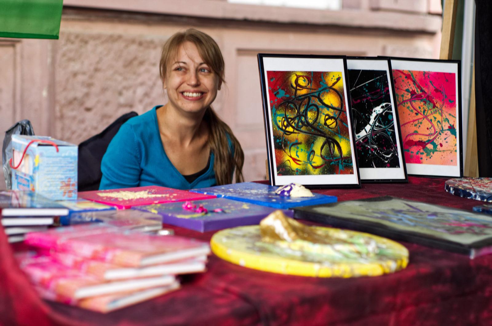Frau Fenster hinter ihrem Präsentationsstand. Sie lächelt, schaut eine Person außerhalb des Bilds an. vor ihr auf dem Tisch Bilder in Rahmen und auf Leinwand, teils plastisch ausgearbeitet