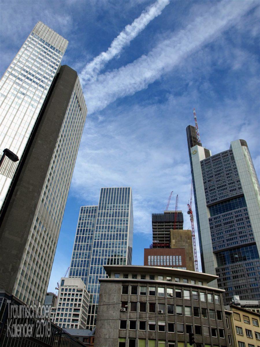 Stadtansicht von Frankfurt. Bild im Hochformat unter blauem Himmel mit Kondensstreifen von Flugzeugen, im Vordergrund Wolkenkratzer, Hoch- und Bürohäuser des Bankenviertels, von den 50er Jahren bis gerade im Bau