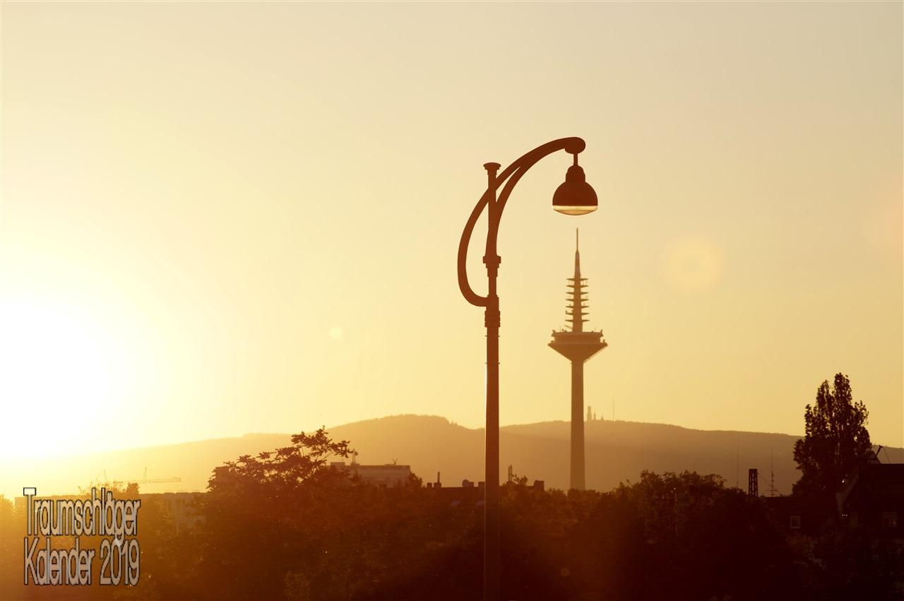 """Landschaftsbild: Von links strahlt hellgelb die tiefstehende Sonne, fängt sich auch leicht in der Objektivlinse. Das Farbspektrum ist dadurch bestimmt und das ganze Bild zeigt sich nur in Gelbtönen und Abstufungen von """"Schatten"""" in graubraun. Zentral im Bild sind mehrere senkrechte Objekte: Eine Straßenlaterne, der Ginnheimer Fernsehturm, der Turm auf dem Großen Feldberg. Je größer das Objekt in Wirklichkeit, desto kleiner erscheint es durch die Perspektive auf dem Foto"""