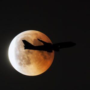 Nachtfoto: Großaufnahme vom Vollmond bzw. Blutmond, er changiert zwischen leuchtend weiß und orangerot. Vor dem Mond zieht als Silhouette ein Flugzeug vorbei, zu erkennen ist nur der Umriss und zwei Positionsleuchten