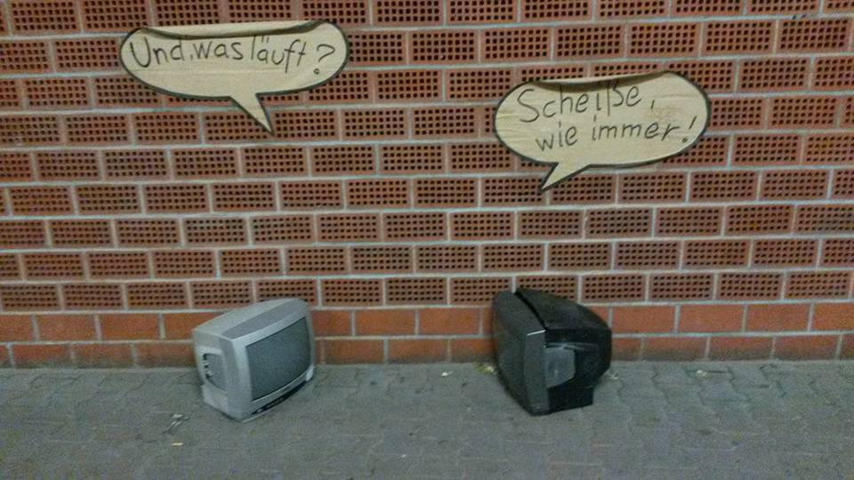 """Zwei abgestellte (defekte?) Fernseher im Straßenraum. An der Wand hinter den Geräten hat jemand Sprechblasen angebracht: """"Und, was läuft?"""" - """"Scheiße, wie immer"""""""