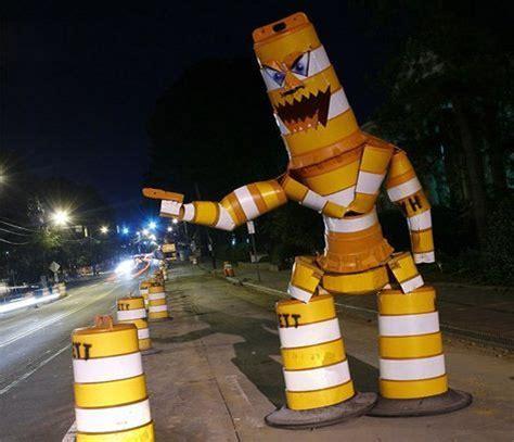 """Neben einer Fahrbahnbegrenzung aus weiß-gelb gestreiften Tonnen steht eine offensichtlich aus solchen Tonnen gebaute Figur. Man erkennt Beine, Rumpf, Arme, einer mit drohend ausgestrecktem Zeigefinger und Kopf. Auf den Kopf wurde noch ein """"Gesicht"""" aufgemalt, mit blauen Augen und aufgerissenem großem Mund mit scharfen Zähnen. Die Figur ähnelt den Figuren aus """"Mechwarrior"""" oder """"Transformers""""."""