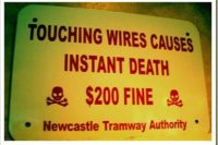 "Warnschild mit Pointe: ""Touching wires causes instant death - $200 Fine. Newcastle Tramway Authority"" - ""Berühren der Drähte führt unmittelbar zum Tode und zu $200 Strafe. Ihre Newscastle Tramway Authority"""