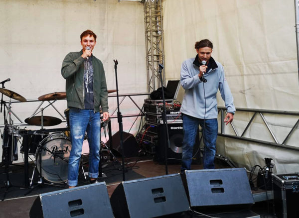 Zwei junge Männer, die mit Improvisations-Rap für ihren HipHop-Workshop einladen