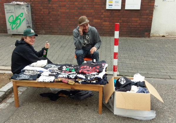Zwei gut gelaunte Männer, davor ein niedriger Tisch und ein Karton mit diversen T-Shirts von Punk-Bands