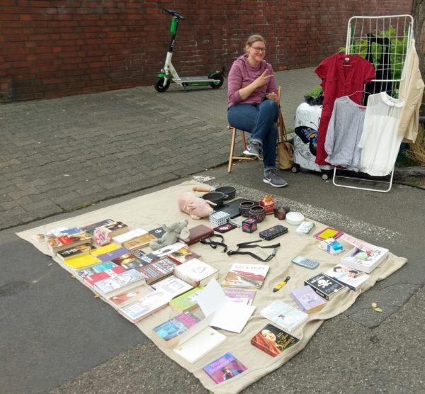 auf einer Decke diverse Gegenstände wie Plüschtiere und Bücher, und eine junge Frau, die diese Dinge anbietet