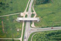 Zunächst nur eine Landstraße mit Einmündung. Über der Kreuzung aber das Fragment einer Brücke. Nur die Straße wird überspannt, das Brückensegment hat keinen Anschluss nirgendwohin.