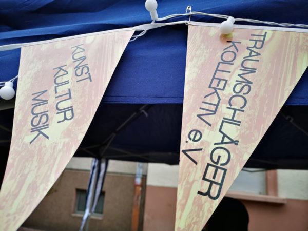 """Ausschnitt vom Pavillon (dunkelblau) mit gelben Wimpeln mit der Aufschrift """"Traumschläger Kollektiv e.V."""" und """"Kunst Kultur Musik"""""""