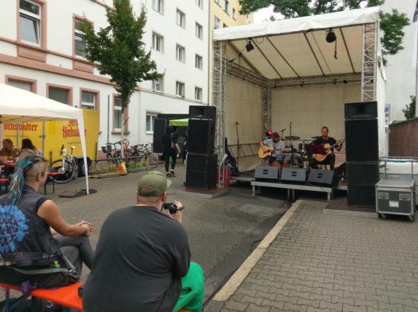 Gäste die zur Bühne schauen, darauf zwei Musiker mit Gitarren, einer singt.