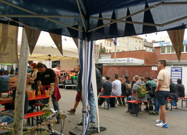 von aus einem Stand fotografiert das laufende Fest, Menschen gehen durchs Bild, viele sitzen auf Bierbänken vor der Bühne, auf der der Singer-Songwriter Yohazid auftritt