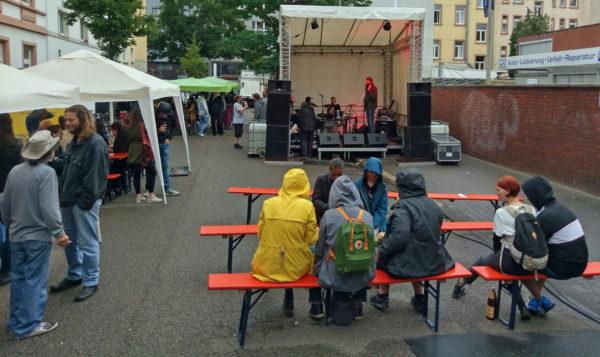 Auf der Bühne stimmen zwei Musiker den Sound ab, Festbesucher sitzen teils unter Pavillons, teils mit Kapuzen auf den Bänken vor der Bühne, da es grade mal wieder nieselt