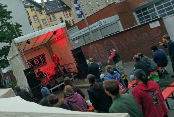 Toy of the Ape spielen live, davor schon viele interessierte Zuhörer auf den Bänken vor der Bühne und stehend