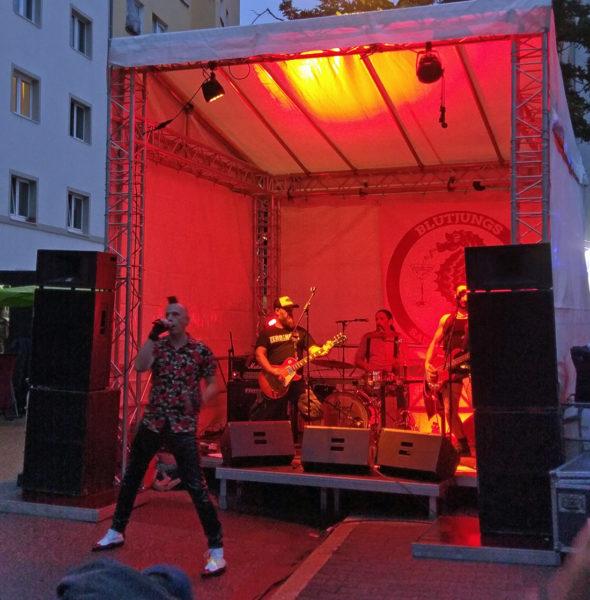 Drei Musiker auf der Bühne, vor der Bühne auf der Straße der Sänger