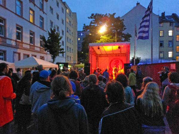 Bild von einigen Metern vor der Bühne über viele Menschen hinweg, die sich das Konzert anhören und anschauen