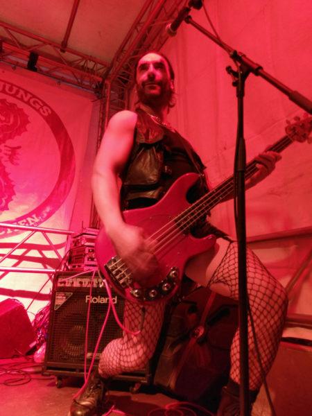 Der Bassist im Bühnenoutfit mit Strümpfen und Hotpants, für die Fotografin hat er eine besonders fotogene Pose eingenommen