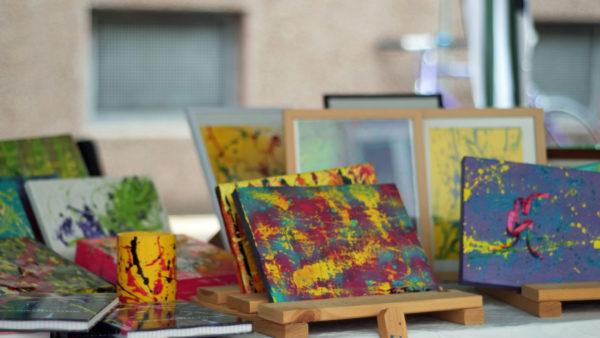 Detailaufnahme eines Kunststands, mit Bildern und Kunstgegenständen, die sehr bunt und farbenfroh gestaltet sind