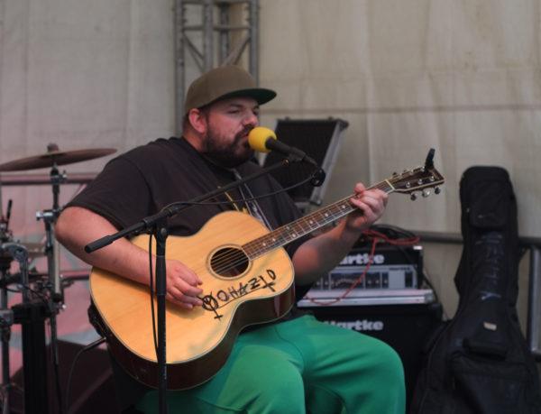 Singer-Songwriter (im weitesten Sinne) Yohazid auf der Bühne, sitzend, mit einer akustischen Gitarre