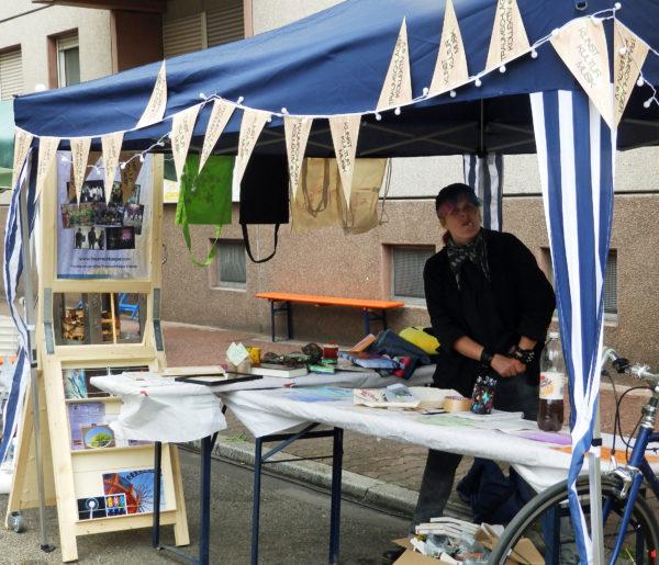 Der Stand des Traumschläger Kollektivs, ein blauer Pavillon mit zwei Tischen und einem großen Holzaufsteller mit Poster, Postkarten und Fotos, auf den Tischen Info-Materialien und die Preise der Tombola