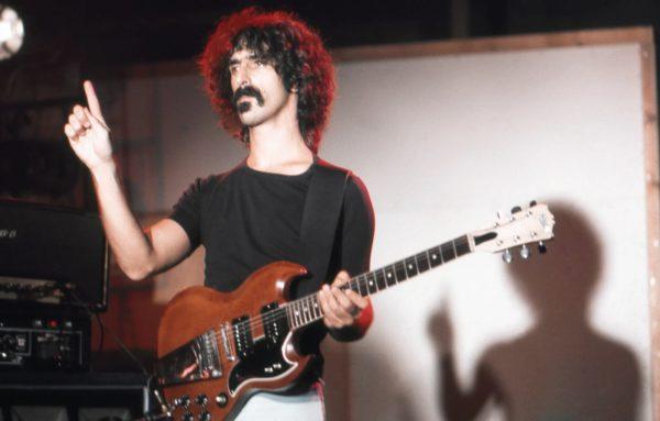 Foto von Frank Zappa. Z. steht im Licht vermutlich eines Scheinwerfers, hat eine E-Gitarre um. Sein Blick geht nach links und er hat den rechten Zeigefinger erhoben.